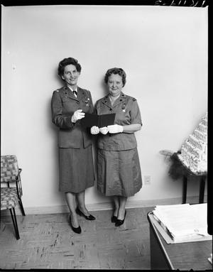Primary view of object titled 'Two Girl Scout Leaders Posing Next to a Cake'.