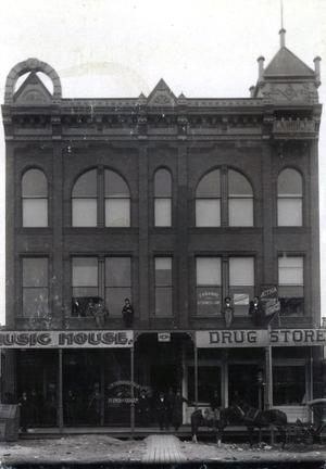 Primary view of object titled 'F.H. Snider Drug Store and The Music House are seen in this street side picture.'.