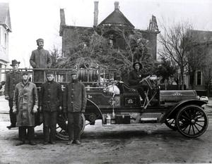 Primary view of object titled 'Firemen and fire truck in front of a house after a fire.'.