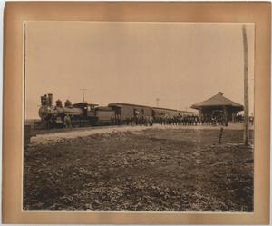 Primary view of object titled 'Train and depot with men standing in front. Unknown location.'.