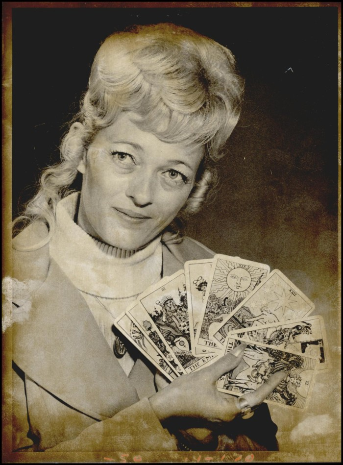 Photograph used for a story in the Daily Oklahoman newspaper. A blond woman holds a deck of tarot cards spread out before the camera. Caption:
