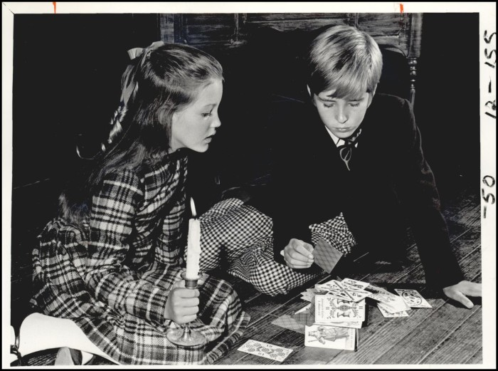 Two children, a boy and a girl, sit looking at tarot cards spread on the floor. The girl holds a candle and the boy holds a card in his hand.