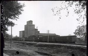 Primary view of object titled 'Cotton Gin Adjacent to the Santa Fe Railroad Tracks in Pauls Valley, Oklahoma'.